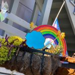 A brightly colored rainbow and cloud sit on a planter box