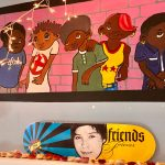 Colorful mural showcasing a group of youth against a pink brick wall. Bellow, on the matle, is a skateboard honoring a LYRIC youth leader.
