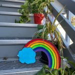 Multi-colored rainbow and a blue cloud prop set up against houseplants in red, green, and black pots.