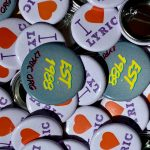 """Pin buttons in lavender and blue denim. Lavender button reads, """"I (heart) LYRIC."""" Blue denim button reads, """"Est. 1998, LYRIC.org."""""""
