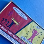 """Archival freamed poster on a blue wall. Poster is split into two panels. Panelon the left is red and and yellow on the right. Red panel sows a group of people hurting an individu with a pink triangle. A person outside of the group is watching and asking themselves, """"Why isn't somebody doing somegthing? On the left panel, the same person says, """"Wait! am somebody!"""" Bottom text reads, """"What have you done to step up?"""