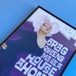 """Archival framed poster on a blue wall. Poster features Ms. Sequoia in dark violet dress and a lavender wig. Text reads, """"Drag queens make a house a home."""""""